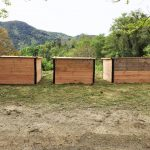 Photo de 3 composteurs partagés en bois installés sur une pelouse