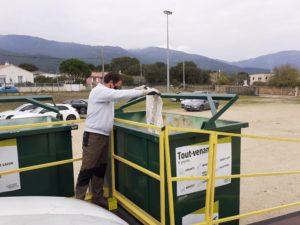 Personne en train de déposer des déchets dans une benne de tout-venant.